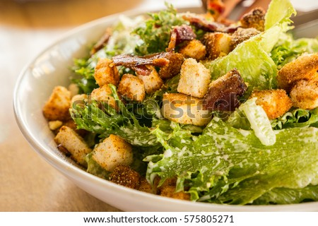 Bowl of Caesar Salad on the wooden table, close up #575805271