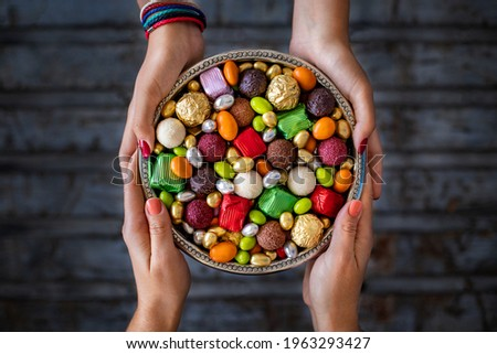 Bowl of candies and chocolate at the hands of two women. Seker bayrami. Many colorful treats .
