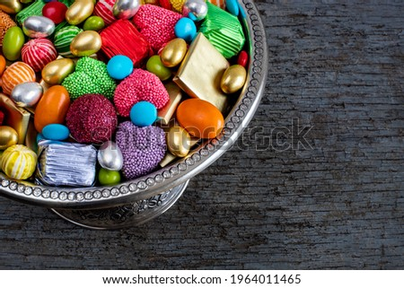 Bowl of candies and chocolate on the wooden table. Many types of candy.