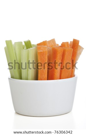 Bowl of carrot and celery sticks isolated on a white background.