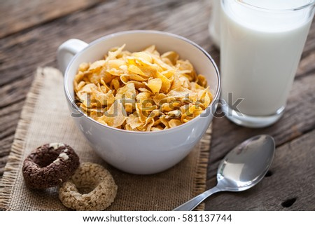 bowl of cereal with milk and cookies on wooden background #581137744