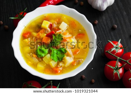 Bowl of chicken soup with vegetables on a dark wooden background #1019321044