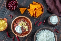 Bowl of chili con carne with toppings on a wooden table