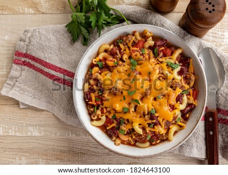 Bowl of chili mac with cheddar cheese on a rustic wooden table.  Overhead view with copy space