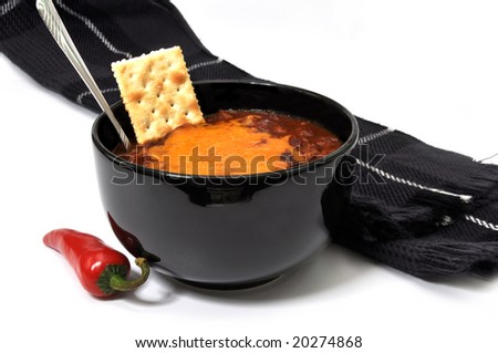 Bowl of chili with melted cheese, cracker, red cayenne pepper, spoon, and scarf.  Isolated on white background.