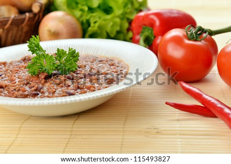 Bowl of chili with peppers and beans