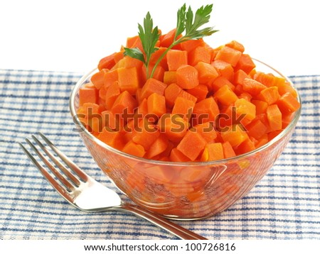 Bowl of chopped carrot on tablecloth on isolated background