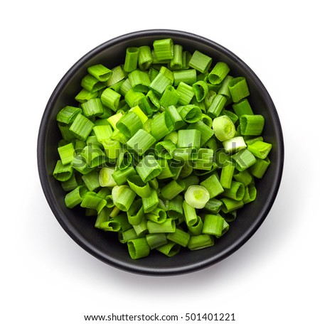 Bowl of chopped spring onions isolated on white background, top view
