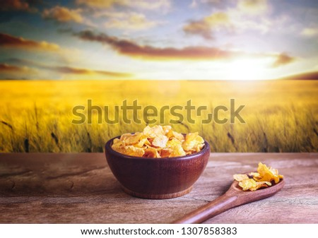 Bowl of cornflakes on rustic background, with wheat field in background in beautiful nature setting. #1307858383