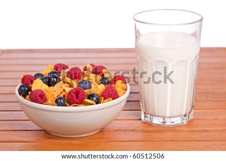 Bowl of cornflakes with fruits and a milk tumbler on white background. Shallow depth of field