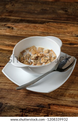 Bowl of cornflakes with milk on brown wooden background #1208339932