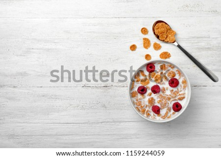 Bowl of cornflakes with milk on light table, top view with space for text #1159244059