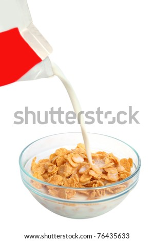 Bowl of cornflakes with pouring milk on white background