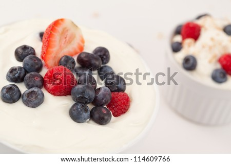 Bowl of cream with different berries against a white background