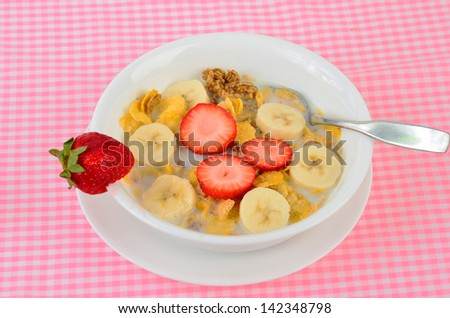 Bowl of crunchy breakfast cereal with bananas and strawberries on pink gingham background.