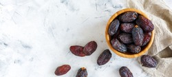 Bowl of dates and a linen cloth on a white concrete background. The view from the top.