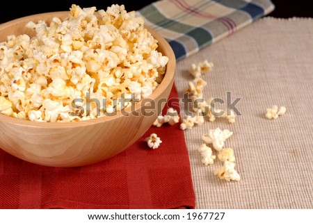 Bowl of delicious popcorn resting on burgundy napkin with popcorn spilling out