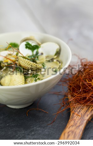 Bowl of delicious savory seafood ragout with fresh coriander leaves, shellfish, garlic and white wine for a gourmet appetizer to dinner