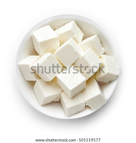 Bowl of diced soft cheese isolated on white background, top view