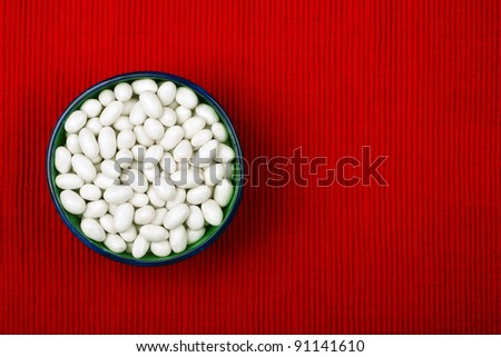 Bowl of dragee on red cloth background