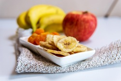 bowl of dried organic banana chips with fresh bananas, dried apricots, Apple. snack