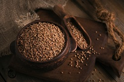 Bowl of dry raw buckwheat groats and wooden scoop on wooden background. Cooking buckwheat porridge concept.
