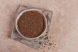 Bowl of dry raw buckwheat groats on light beige background. Cooking buckwheat porridge concept. Top view