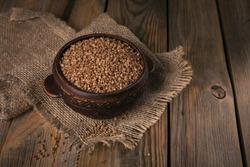 Bowl of dry raw buckwheat groats on wooden background. Cooking buckwheat porridge concept.