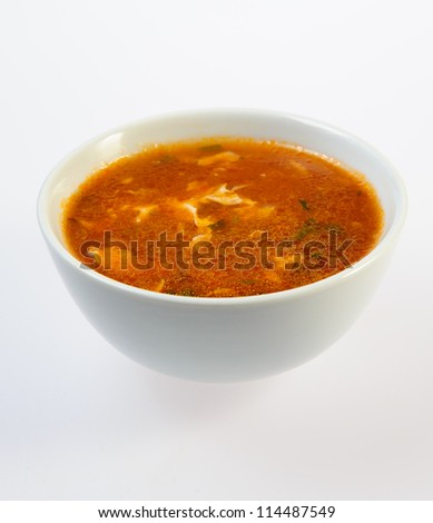 Bowl of fish soup over white background