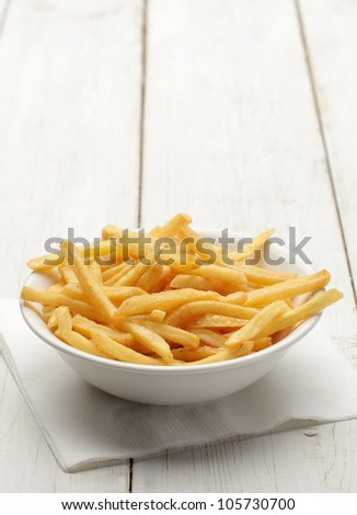 bowl of french fries on white wooden surface