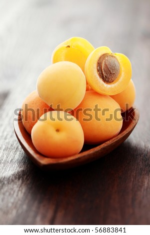 bowl of fresh apricots on wooden table - fruits and vegetables