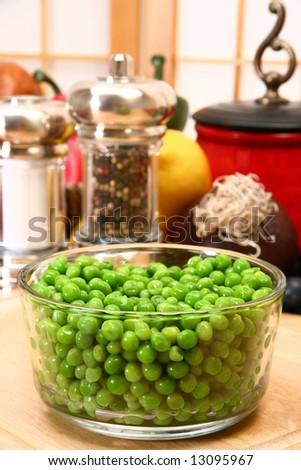 Bowl of fresh green peas in kitchen or restaurant.