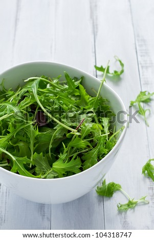 Bowl of fresh green salad on a white table