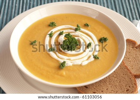 Bowl of fresh hot butternut soup with cream and parsley, served with rye berliner bread