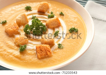 Bowl of fresh hot butternut soup with cream, parsley and croutons