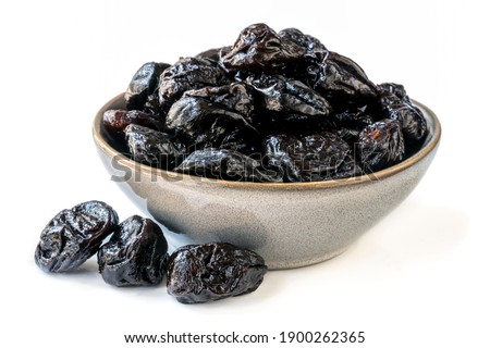 Bowl of fresh juicy pitted prunes over white background. Stockfoto ©