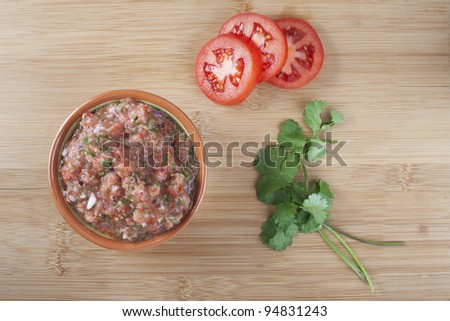 Bowl of fresh salsa with tomato slices and cilantro viewed from directly above.