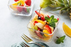 Bowl of fresh summer fruit salad on white stone background. Healthy food. Copy space