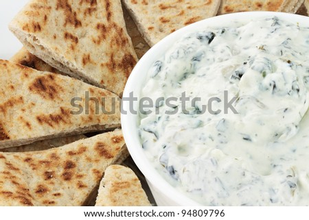 Bowl of fresh vegetarian spinach dip served with wedges of pita bread for a healthy snack.