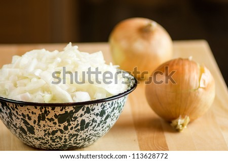 Bowl of freshly chopped onions with onions on cutting board