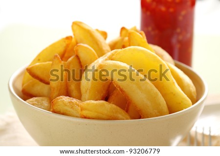 Bowl of freshly fried crisp potato wedges ready to serve.