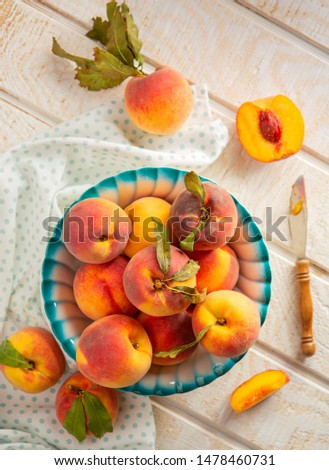 Bowl of freshly picked yellow peaches on a white wooden surface