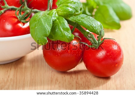 Bowl of freshly washed vine tomatoes with basil herbs