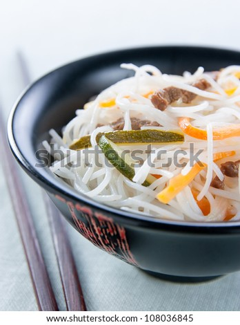 Bowl of fried rice noodles with vegetables, mushrooms and meat