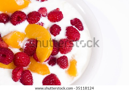 Bowl of fruit with yogurt peaches, rasberrys