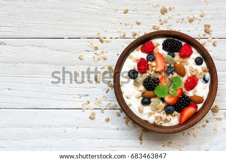 bowl of greek yogurt with granola, oats, berries and nuts for healthy breakfast. top view