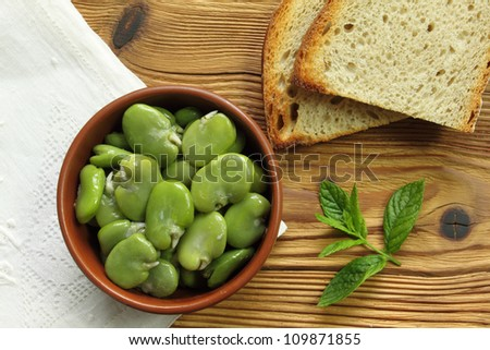Bowl of green boiled broad beans and bread