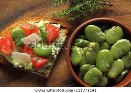 Bowl of green boiled broad beans and sandwich