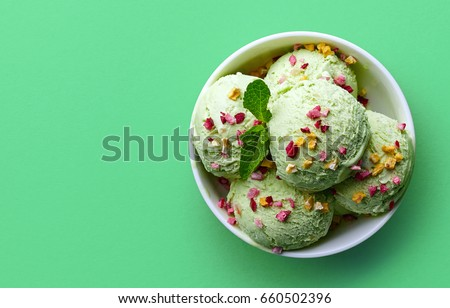 Bowl of green pistachio ice cream and dried fruit pieces isolated on green background. Top view