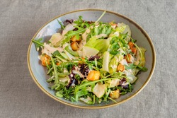 Bowl of green salad with apple slices, cheese slices, croutons, arugula and lettuce sprouts with mayonnaise sauce on gray linen tablecloth